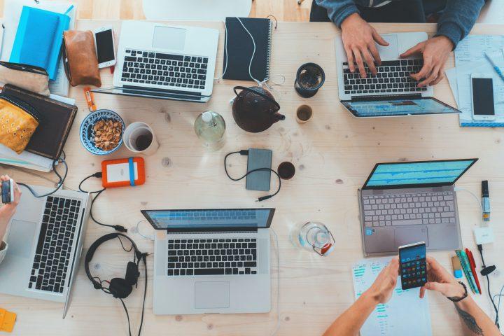 人々が寄り集まってパソコンで作業している様子。